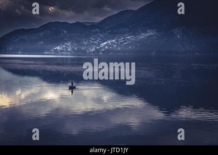 Idyllic mountains landscape with man in fishing boat in the middle of tranquil lake with water reflections during - Stock Photo
