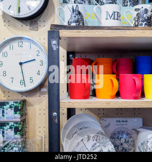 Coloured mugs and wall clocks on sale in a shop in Spitalfields Market. London 2017. - Stock Photo