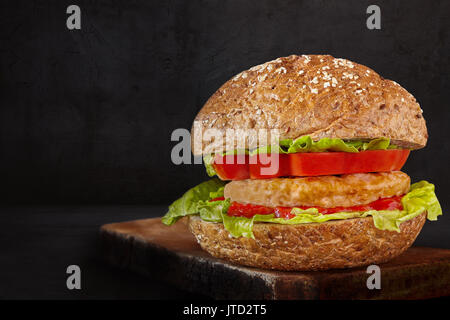 Hamburger made with meat, lettuce, tomato, ketchup and seeds bun, on black background. - Stock Photo