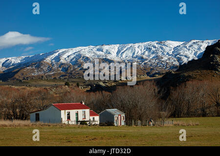 Old cottages and Rock and Pillar Range, Sutton, near Middlemarch, Strath Taieri, Otago, South Island, New Zealand - Stock Photo