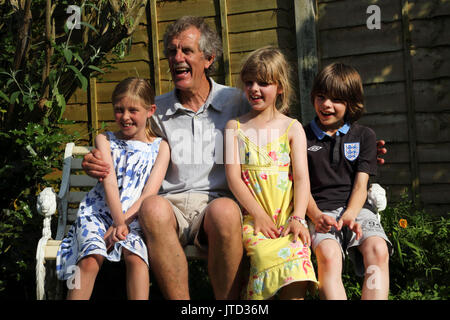 Grandfather With His Grandchildren sitting on Bench Smiling In Garden During Summer Birmingham West Midlands England - Stock Photo