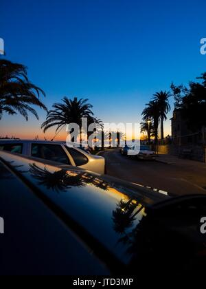 Solin Vranjic near Split in Croatia sunset parked car cars glass windshield reflections - Stock Photo
