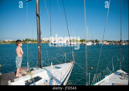 one healthy happy small boy wearing sunglasses aboard luxury boat in port - Stock Photo