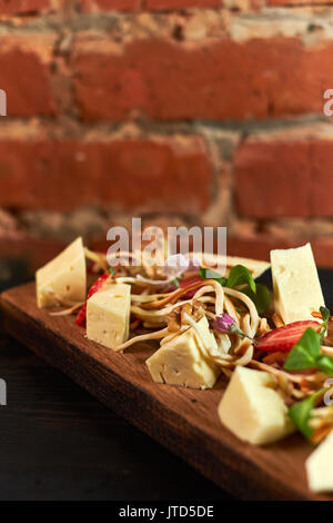 Pieces of cheese on a board with vegetables hd - Stock Photo