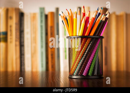 Wire desk tidy full of coloured pencils standing on a wooden table in front of a bookshelf full of books with shallow - Stock Photo