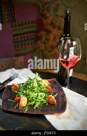 Salad with shrimps and arugula serve on a table with wine - Stock Photo
