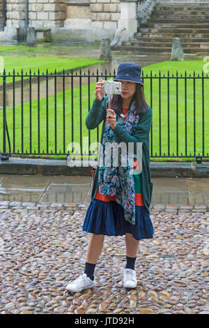 Tourist takes a selfie in front of Radcliffe Camera at Oxford, Oxfordshire in August on a wet rainy day - Stock Photo