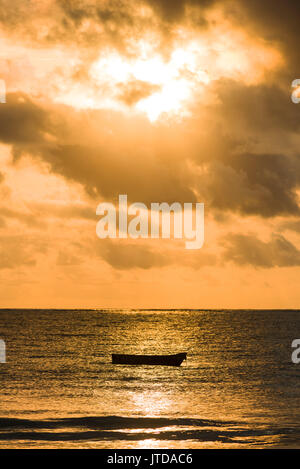 Dhow boat silhouetted in early morning sunlight breaking through clouds over Indian ocean, Diani, Kenya - Stock Photo