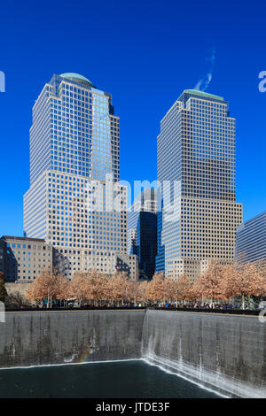 The view across the 9/11 Memorial site to Two and Three World Financial Centers in New York City. - Stock Photo