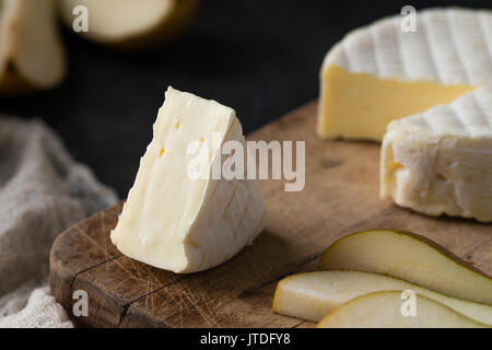 Closeup of French soft cheese from Normandy region sliced with pear on a wooden board on dark rustic background - Stock Photo