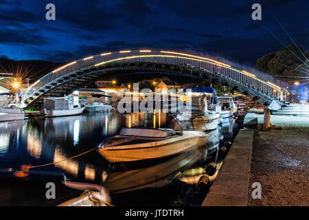 Arched bridge for pedestrians in Trogir, Croatia, Unesco. Night scene. Travel destination. Boats in the port. - Stock Photo