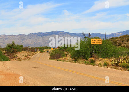 Do not enter when flooded flash flood area warning sign on a roadside in Arizona with mountains in the background. - Stock Photo