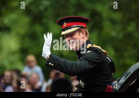 HRH Prince Harry smiles and waves at the crowds lining The Mall during the Trooping the Colour carriage  procession. - Stock Photo