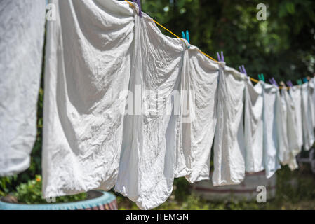Washed pillowcase hanging on rope and dry in the sun. Ukraine - Stock Photo