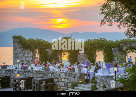 NJIVICE, CROATIA - JUNE 24, 2017 : A restaurant terrace on the waterfront full of people at sunset on island Krk - Stock Photo