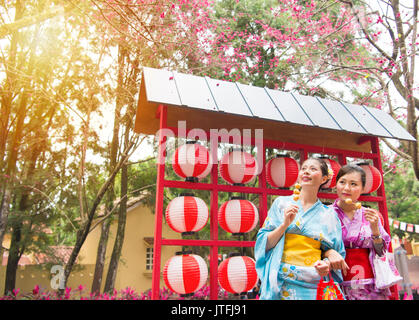 smiling traditional kimono girls eat fried meatballs skewer standing in front of the cultural celebration lanterns - Stock Photo
