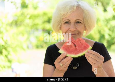 Mature woman eating watermelon. - Stock Photo