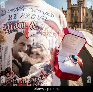 A royal fan outside Westminster Abbey in London displays a replica of Kate Middleton's engagement ring two days - Stock Photo
