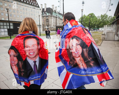 Royal fans wrapped in William and Kate celebration flags on the day of the Royal wedding of Prince William Wales - Stock Photo