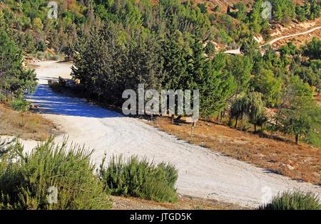 Rocky dirt road winding beside the Judean desert wilderness as seen from Mt. Scopus in Jerusalem, Israel. - Stock Photo