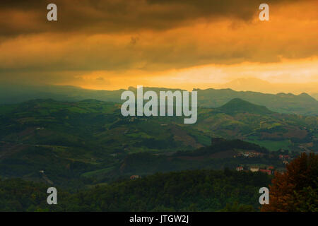 Sunset view on Italy from San Marino. Beautiful landscape of italian green lands with stunning yellow sky and mountain - Stock Photo