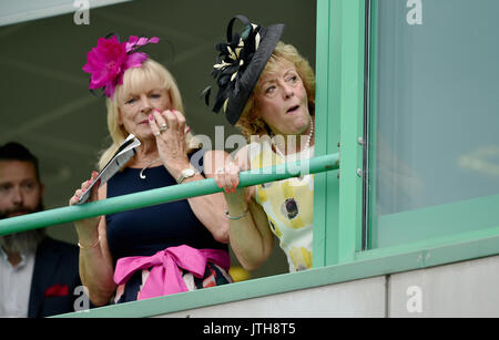 Brighton, UK. 9th Aug, 2017. These racegoers stay warm and dry before the rain arrives at the Marstons Race Day - Stock Photo