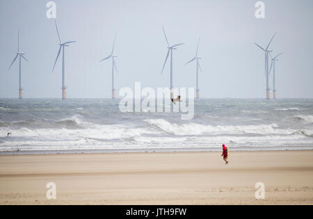 Lifeguard patrolling an empty beach on a very windy August day at Seaton Carew, County Durham, north east  England, - Stock Photo