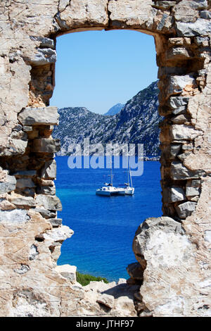 View on yachts in Aergean sea through the ancient window - Stock Photo