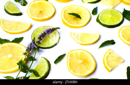 Lemon and lime slices with mint leaves on white - Stock Photo
