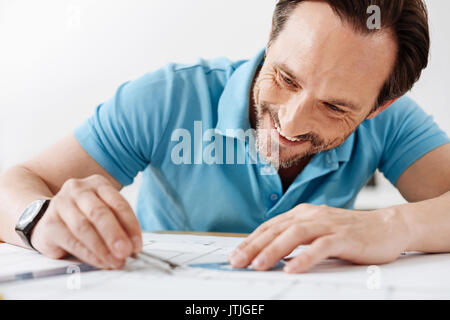 Bristled man taking measurements with a compass - Stock Photo