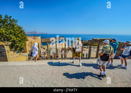 Tourists enjoy the beautiful view of the Mediterranean sea from the ancient ruins of the Lindos Acropolis on the - Stock Photo