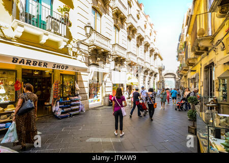 Tourists and locals shop and wander the Corso Umberto, main street in the resort town or Taormina Italy on the island - Stock Photo