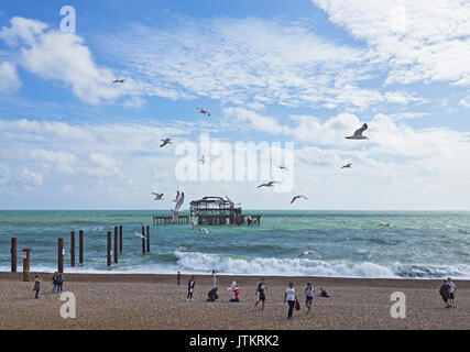 Brighton beach and the remains off the West pier with people enjoying the beach and sun with the local seagulls - Stock Photo
