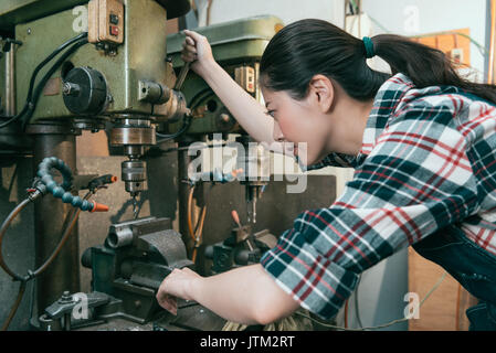 smiling young lady engineer working in factory milling machining department and adjustment industrial machines to - Stock Photo