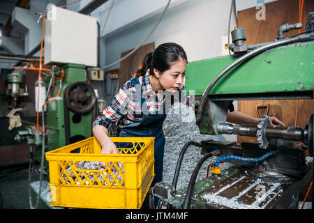 young lathe female worker looking closely at machine and put in yellow basket parts components seriously working - Stock Photo