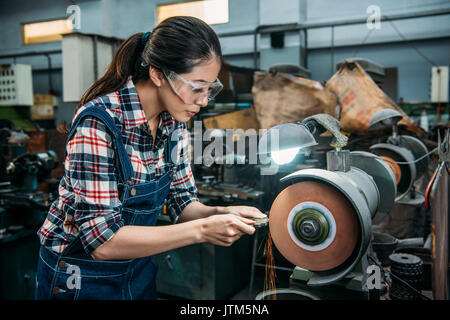 attractive lathe female worker holding components metal grinding and wearing safety glasses working on grinding - Stock Photo