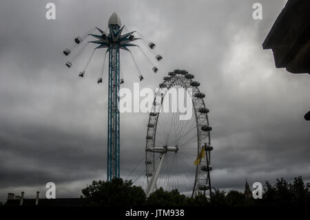 Overcast, cloudy day in London with a view of an amusement park ride and the London Eye ferris wheel against the - Stock Photo
