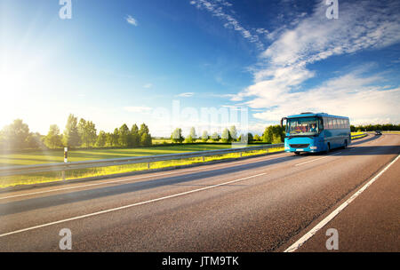 Bus on asphalt road in beautiful summer evening