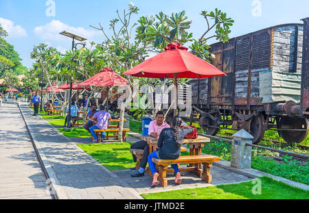 COLOMBO, SRI LANKA - DECEMBER 7, 2016:  The crowded outdoor cafe next to the freight train from the Fort Railway - Stock Photo