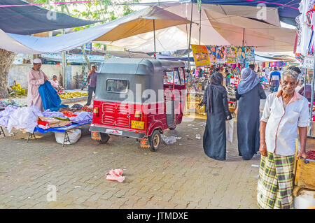 NEGOMBO, SRI LANKA - DECEMBER 7, 2016: The old clothes market in residential district of the city, tuk-tuk is parked - Stock Photo