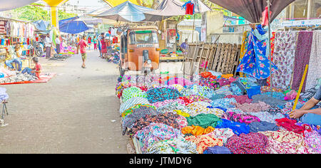 NEGOMBO, SRI LANKA - DECEMBER 7, 2016: The colorful women clothes in old market in residential district of the city, - Stock Photo