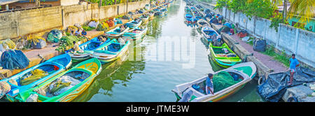 NEGOMBO, SRI LANKA - DECEMBER 7, 2016: The numerous fishing boats on Hmilton's Canal with nets on the banks, on - Stock Photo