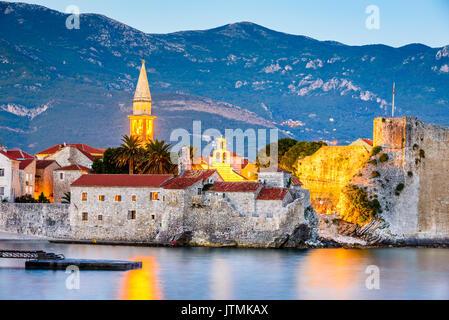 Budva, Montenegro. Ancient walls with Adriatic Sea, illuminated in twilight. - Stock Photo