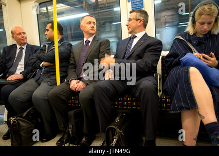 London Underground. Business men on the Circle Line next to a woman wearing headphones on her phone - Stock Photo