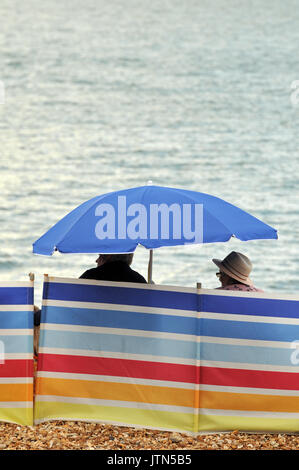 two middle aged people or an older couple sitting behind a wind brak under a sun shade on the beach at the seaside - Stock Photo