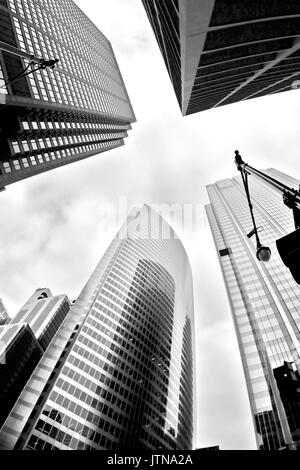 Glass skyscrapers against cloudy sky in the city of Chicago, Illinois, USA. Black and white abstract upward view of downtown skyscrapers.