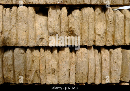 Stacks of gold coloured walling or coping stone for finishing off the top of a wall - Stock Photo