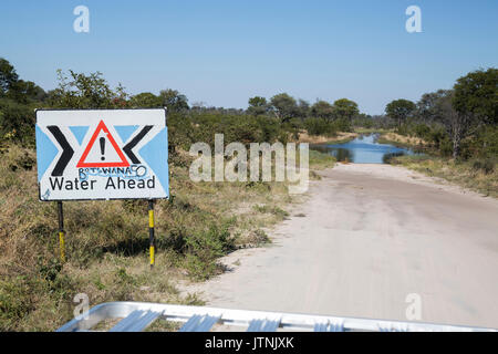 Roadsign warning of a flooded road ahead in Northern Botswana - Stock Photo