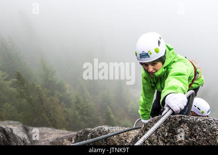 A women reaches for the metal rung while climbing the Via Ferrata in Squamish, British Columbia. - Stock Photo