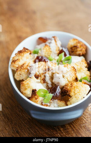 Roasted Cauliflower with Dates and Tahini Dressing - Stock Photo